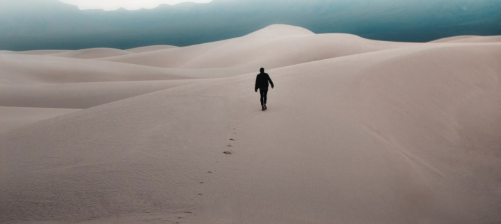 Man walking in desert, tracks in sand