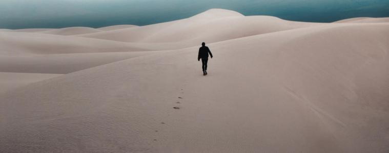 Man walking in desert, tracks in sand