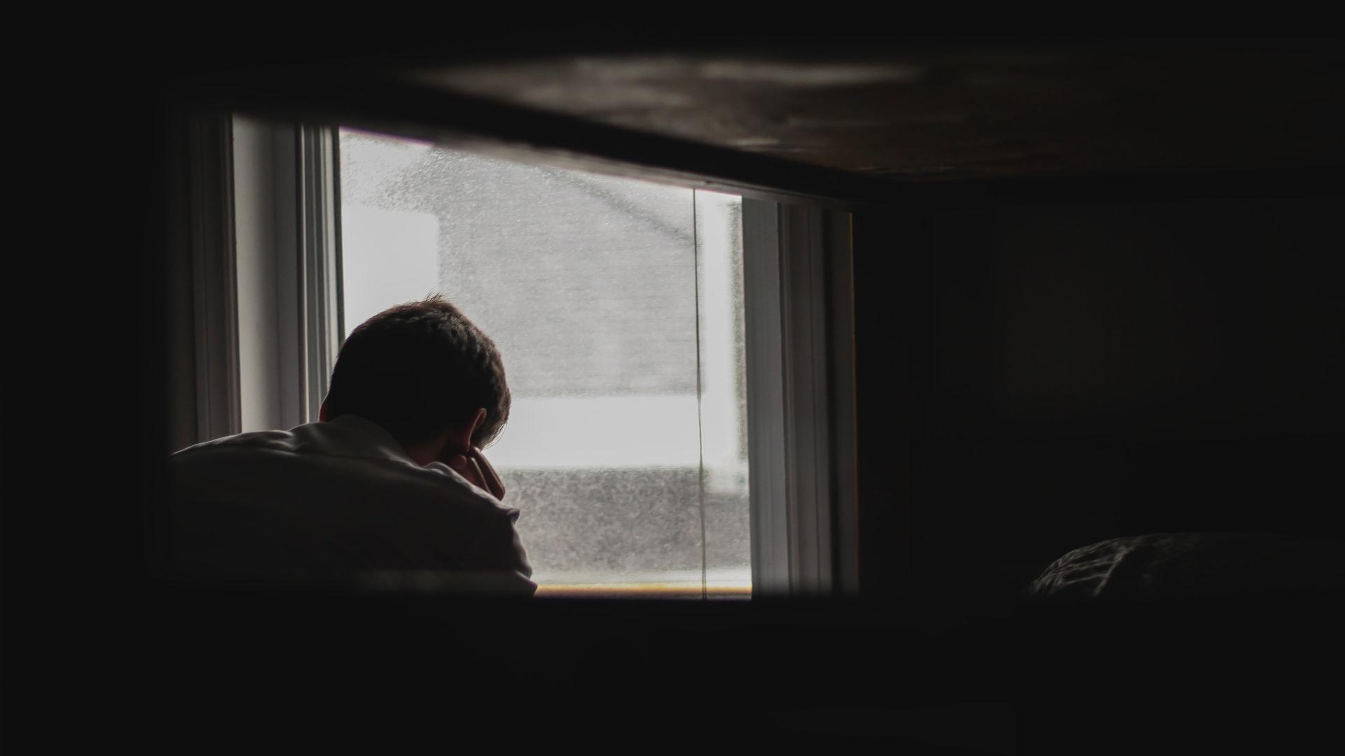 Man waiting by window, sigh